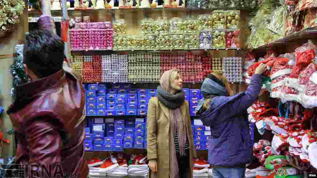 این خانواده هم در یک فروشگاه وسایل کریسمس در تهران مشغول انتخاب وسایل است. عکس: عبدالله حیدری، ایرنا