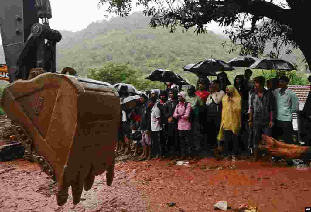 Dân làng Ấn Độ đứng xem hoạt động cứu nạn tại địa điểm xảy ra một vụ lở đất lớn tại làng Malin ở huyện Pune trong bang Maharashtra thuộc miền tây.