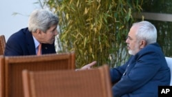 FILE - U.S. Secretary of State John Kerry, left, talks with Iranian Foreign Minister Mohammad Javad Zarif, in Geneva, Switzerland, May 30, 2015.
