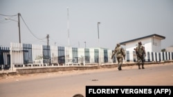 Deux soldats centrafricains patrouillent dans le quartier vide de PK12, à 12 kilomètres du centre-ville de Bangui, le 13 janvier 2021.