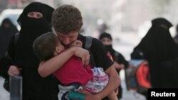 Một người dân đang ẵm một đứa trẻ sau khi họ được Lực lượng Dân chủ Syria SDF sơ tán khỏi Manbij, khu vực bị Nhà nước Hồi giáo kiểm soát ở Aleppo, Syria, ngày 12/8/2016.