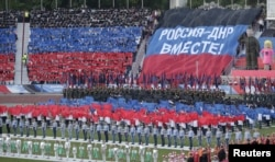 """People gather at a stadium during celebrations marking the fourth anniversary of Donetsk's self-declared independence in Donetsk, Ukraine, May 11, 2018. The banner reads: """"Russia - DNR together!"""" DNR is the initialism for the Donetsk People's Republic."""