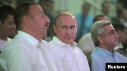 Presidents Vladimir Putin (C) of Russia, Serzh Sargsyan (R) of Armenia and Ilham Aliyev of Azerbaijan attend an international sambo tournament in Sochi August 9, 2014. Azerbaijan and Armenia accused each other on Monday of stoking tensions over the breaka