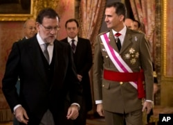 FILE - Spain's King Felipe VI walks with Spain's Prime Minister Mariano Rajoy, left, during the annual Pascua Militar Epiphany ceremony at the Royal Palace in Madrid, Spain, Jan. 6, 2016. Spain's king is meeting Tuesday with the country's political parties.