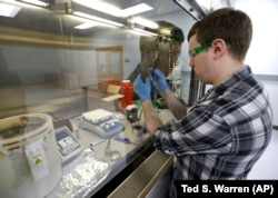 Caleb Ogier, a PhD student in mechanical engineering at the University of Washington, works in a fume hood with ink used to produce electrical circuits, at the newly opened Washington Clean Energy Testbeds laboratory.