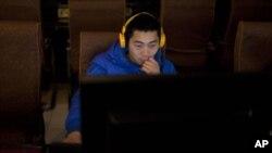 Un usuario navega por la web utilizando la computadora de un café-internet en el centro de Pekín.