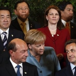 German Chancellor Angela Merkel, center, speaks with French President Nicolas Sarkozy, front right, and Romania's President Traian Basescu, front left, during a group photo at an ASEM 8 summit in Brussels (File Photo)