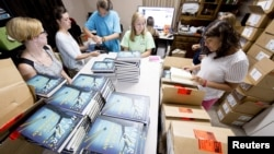 "Para pegawai toko buku Ol' Curiosities & Book Shoppe di Monroeville, Alabama, mengeluarkan buku-buku ""Go Set A Watchman"" dari dalam kardus (14/7)."