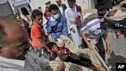 在周六与警方冲突后,也门反政府抗议者抬着一名受伤者