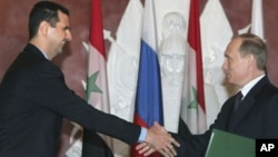 Syrian President Bashar Assad and Russian President Vladimir Putin shake hands during ceremony, the Kremlin, Jan. 2005 (file photo).