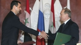 In this Jan. 25, 2005 file photo, Syrian President Bashar Assad, left, and Russian President Vladimir Putin shake hands during a signing ceremony in the Kremlin, Moscow.