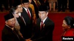 PresidenJoko Widodo (dua dari kanan) didampingi ibu negara, Iriana (kanan) menyalami Menteri Ekonomi yang baru saja dilantik Darmin Nasution (kanan) setelah diambil sumpahnya di Istana Presiden, Jakarta, 12 Agustus 2015 (Foto: REUTERS/Darren Whiteside).