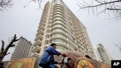 一男子骑车经过中国上海某处刚建好的居民楼