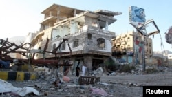 FILE - People walk past a building destroyed during recent fighting in Yemen's southwestern city of Taiz, March 14, 2016.