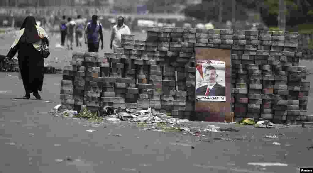 Members of the Muslim Brotherhood and supporters of deposed Egyptian president Mohamed Mursi walk around makeshift barricades near Cairo's Rabaa el-Adawiya Square July 28, 2013