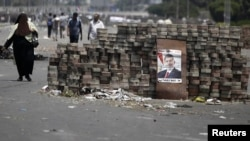 Members of the Muslim Brotherhood and supporters of deposed Egyptian president Mohamed Morsi walk around makeshift barricades near Cairo's Rabaa el-Adawiya Square July 28, 2013.