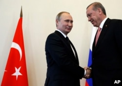 FILE - Russian President Vladimir Putin, left, welcomes Turkish President Recep Tayyip Erdogan in the Konstantin palace outside St.Petersburg, Russia, Aug. 9, 2016.