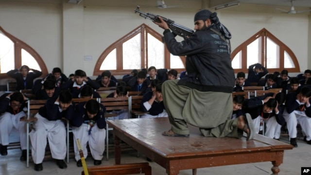 A Pakistani security official poses as a militant during a security drill Feb. 2 at the Islamia College in Peshawar.