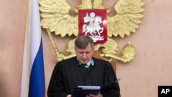 FILE - Russia's Supreme Court judge Yuri Ivanenko reads the decision in a court room in Moscow, Russia, April 20, 2017. Russia's Supreme Court has rejected an appeal of its nationwide ban on the Jehovah's Witnesses.