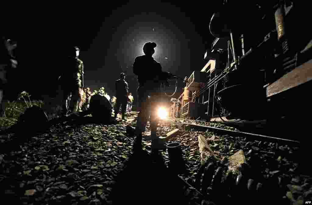 11/7: Một nhân viên an ninh Ấn Độ đứng cạnh một toa xe lửa bị trật đường rầy gần Bhatkuchi, Ấn Độ. 50 hành khách bị thương sau khi 4 toa tàu của chuyến xe lửa tốc hành Guwahati-Puri bị trật đường rầy. Có tin cho hay, tai nạn xảy ra sau một vụ nổ.