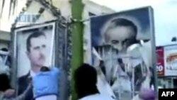 Người biểu tình ở Syria xé bích chương hình Tổng thống Bashar Assad (trái), và cha của ông là ông Hafez Assad, ngày 29 tháng 4, 2011