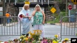 دو زن در محل یابود قربانی کشته شده در درگیری های روز یکشنبه.