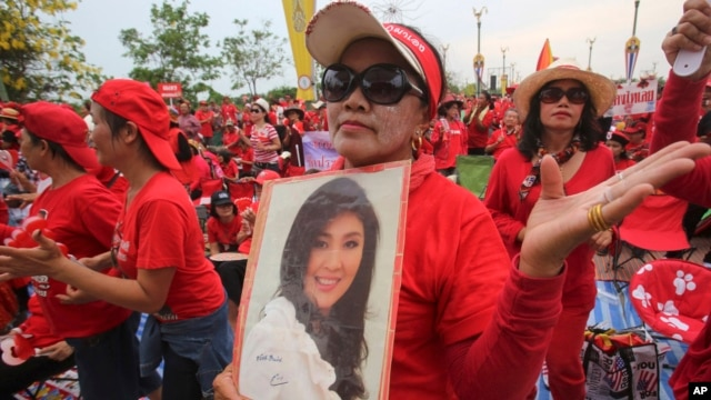 A pro-government Red Shirt member dances with a portrait of Thai Prime Minister Yingluck Shinawatra during a rally in Bangkok, April 5, 2014.
