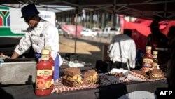 """Un marchand de rue prépare un sandwich """"Kota"""" lors du festival de Kota, à Kliptown, à Soweto, le 8 septembre 2018."""
