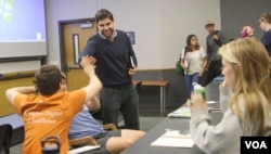Carlos Galdeano (standing) high fives a student