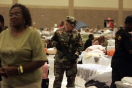 FILE - After Hurricane Katrina, an armed National Guard soldier patrols a Red Cross shelter in Baton Rouge, Louisiana, Oct. 4, 2005.