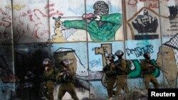 8月13日在约旦河西岸拉马拉市附近查拉迪亚的一个检查哨卡,以色列士兵对巴勒斯坦人抗议以色列攻击加沙的示威保持警戒。
