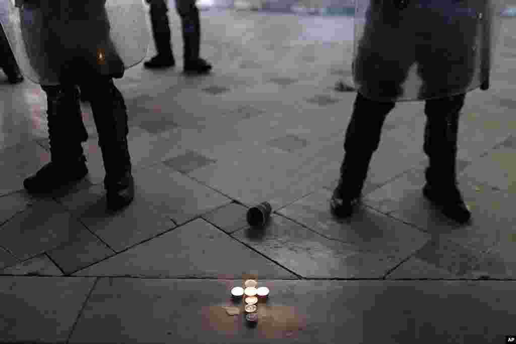 Candles forming a cross sit in front of the tomb of the unknown soldier as riot police secure the Greek Parliament, during a protest in Athens, April 4, 2012. (AP)