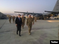 U.S. Sen. John McCain of Arizona walks with American service personnel as an EC-130H Compass Call, deployed from a base in his home state of Arizona, is prepared for a mission.