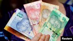 Photo d'archives: Le Gouverneur de la banque centrale sud-africaine tenant de nouveaux billets de banque, 6 novembre 2012 - REUTERS/Siphiwe Sibeko