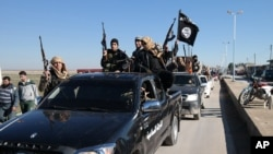 FILE - Islamic State militants pass by a convoy in Tel Abyad town, northeast Syria.