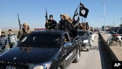 Islamic State militants pass by a convoy in Tel Abyad town, northeast Syria, in this photo released May 4, 2015, by a militant website.