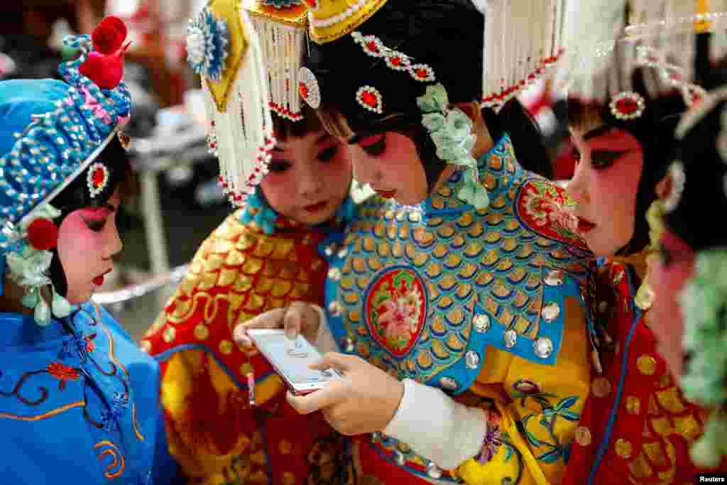 អ្នកចូលរួមម្នាក់លេងហ្គេមនៅលើទូរស័ព្ទរបស់នាង ខណៈដែលអ្នកដទៃមើលនាងក្នុងពេលសម្រាកមួយនៅក្នុងការប្រកួតល្ខោន Opera ប្រពៃណីរបស់ចិននៅមជ្ឈមណ្ឌល National Academy of Chinese Theatre Arts ក្នុងក្រុងប៉េកាំង ប្រទេសចិន កាលពីថ្ងៃទី២៦ ខែវិច្ឆិកា ឆ្នាំ២០១៦។