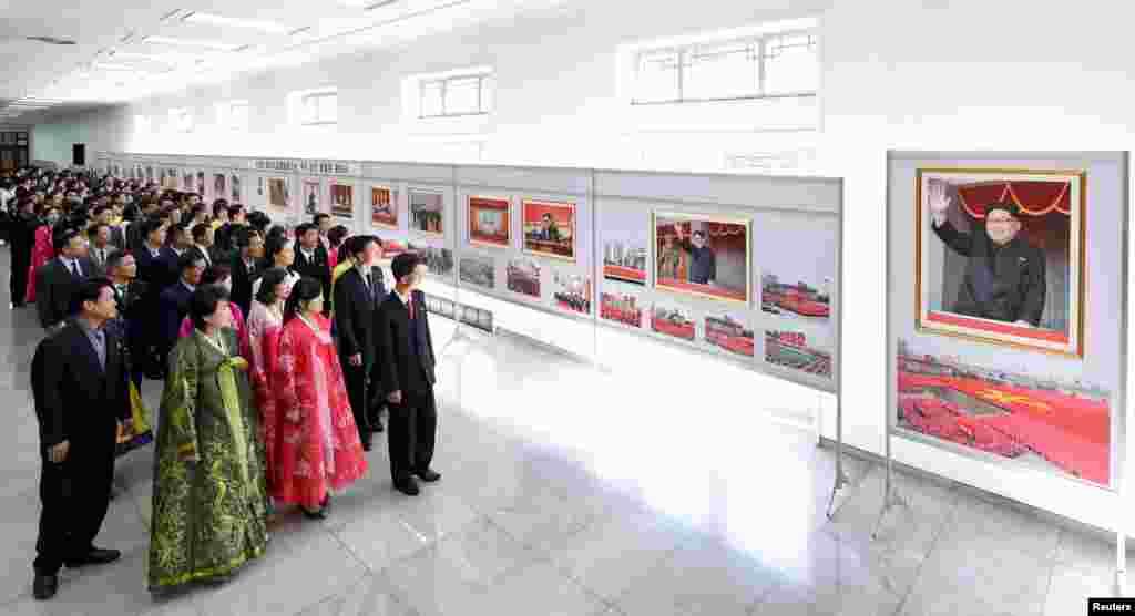 ទស្សនិកជនកំពុងមើលរូបថតមួយដែលត្រូវបានគេដាក់តាំងនៅក្នុងការតាំងពិរព័ណ៌មួយអបអរការជាប់ឆ្នោតរបស់លោកគីម ជុងអ៊ីលជាអគ្គលេខាធិការរបស់គណបក្ស Workers' Party of Korea នៅក្នុងវិមានវប្បធម៌ប្រជាជន។