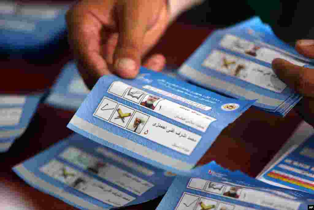 An Afghan election commission worker sorts ballots for an audit of the presidential run-off at an election commission office in Kabul, Aug. 25, 2014.