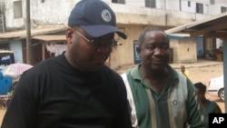 FrontPage Africa editor Rodney Sieh (left) escorted by a marshal (right)
