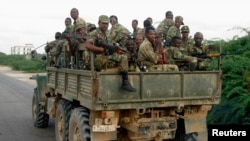 Ethiopian soldiers ride on an army truck on the road to Afgooye settlement, about 30km (19 miles) south of Somalia's capital Mogadishu January 24, 2007.