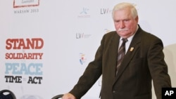 FILE - Former Polish president Lech Walesa is seen standing between chairs after a news conference in Warsaw, Poland, Oct. 20, 2013.