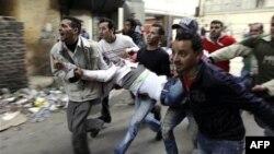 Người Ai Cập khiêng một người biểu tình bị thương trong cuộc đụng độ với cảnh sát ở Cairo