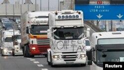 Para supir truk Perancis berdemonstrasi memprotes pajak kendaraan berat di jalan di luar kota Lyon, Perancis (16/11). (Reuters/Robert Pratta)