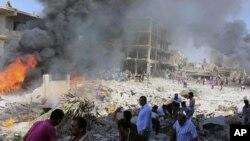 Residentes sirios se reunieron en el lugar donde dos explosiones impactaron la ciudad de Qamishli, Siria, el miércoles, 27 de julio de 2016.