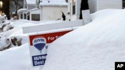 Un cartel de venta de una casa casi tapado por la nieve en Marlborough, Massachusetts.