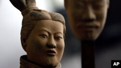 FILE - A female terracotta soldier statue holds the mask of a man as it stands in an army made up of women and children at an art gallery in Beijing, Feb. 24, 2007. Women in China say they are seeing an eroding of their status from the days of Mao Zedong