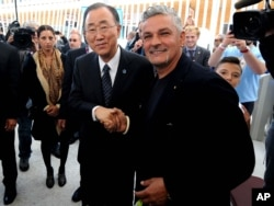 United Nations Secretary-General Ban Ki-moon, left, shakes hands with Italian soccer legend Roberto Baggio, at the Expo World's Fair on the occasion of the UN World Food Day in Rho, near Milan, Italy, Friday, Oct. 16, 2015.