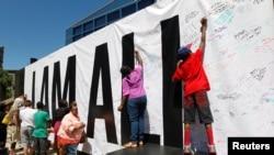 """Para penggemar almarhum Muhammad Ali menandatangani spanduk raksasa dalam acara """"I Am Ali"""" untuk merayakan kehidupan sang juara di Kentucky Center of the Performing Arts, Louisville, Kentucky (8/6)."""
