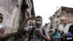 Un homme porte un masque à gaz lors de manifestations encouragées par l'église catholique à Kinshasa, le 25 février 2018.